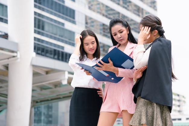 Líder empresaria busca error de informe financiero de colegas mientras camina regresa a trabajar en la oficina