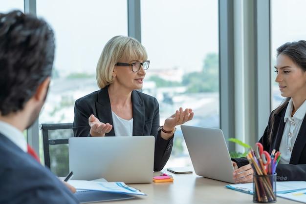 Líder de empresaria senior hablando con colegas mientras se reúne en la oficina. presentación de la reunión del equipo de negocios
