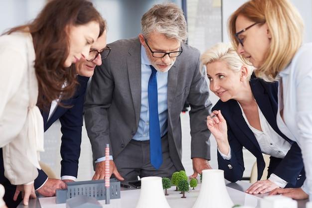 Líder empresarial escuchando atentamente el discurso de compañeros de trabajo