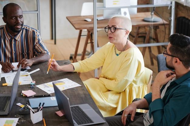Líder empresarial femenina en vestido elegante hablando con sus empleados y dándoles instrucción en el trabajo durante una reunión en la oficina