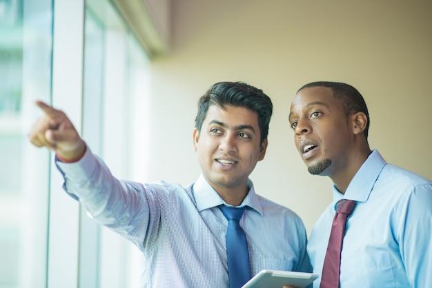 Líder empresarial joven que muestra el edificio vecino al inversor
