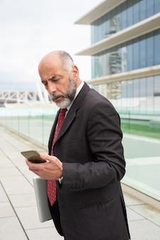 Líder empresarial maduro enfocado con mensaje de lectura portátil