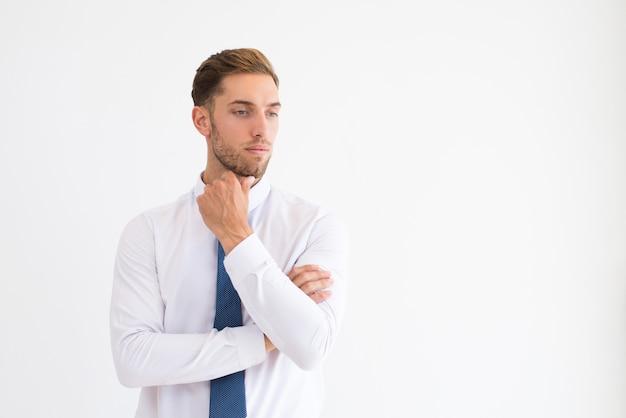 Líder empresarial pensativo tocar la barbilla y mirando a la cámara