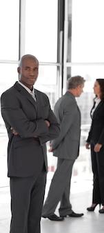 Líder empresarial serio con los brazos cruzados mirando la cámara frente al equipo