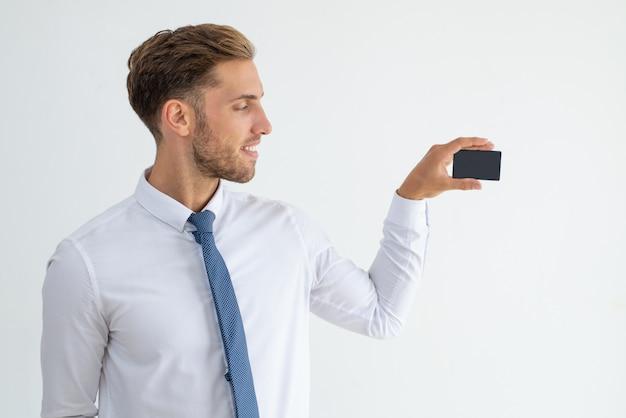 Líder empresarial sonriente que muestra la tarjeta de visita en blanco