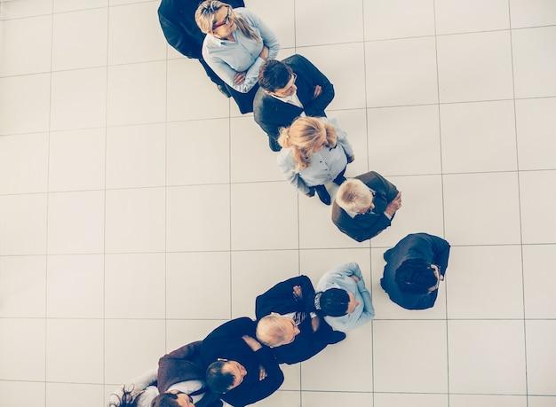 Líder empresarial de vista superior de pie delante de sus colegas