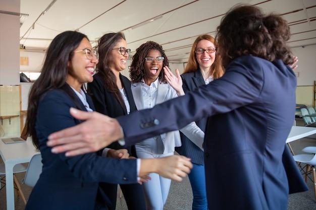 Líder del equipo abrazando a sus felices colegas más jóvenes