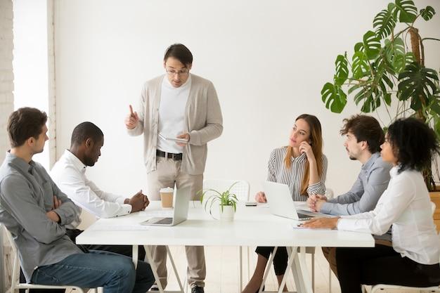 Líder del equipo caucásico reprendiendo al empleado africano por error en la reunión