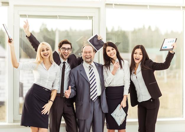 Líder y equipo empresarial exitoso animando después de firmar un lucrativo contrato financiero.