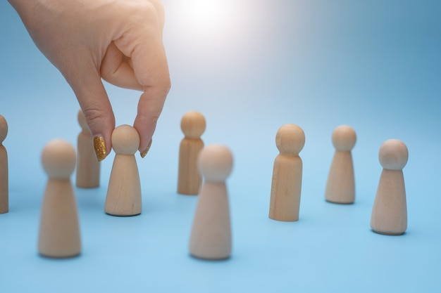 Líder de equipo exitoso, la mano de la mujer elige a las personas que se destacan del otro.