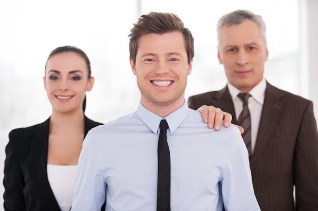 Líder de equipo real. hombre joven alegre en ropa formal mirando a la cámara y sonriendo mientras sus colegas de pie detrás de ella