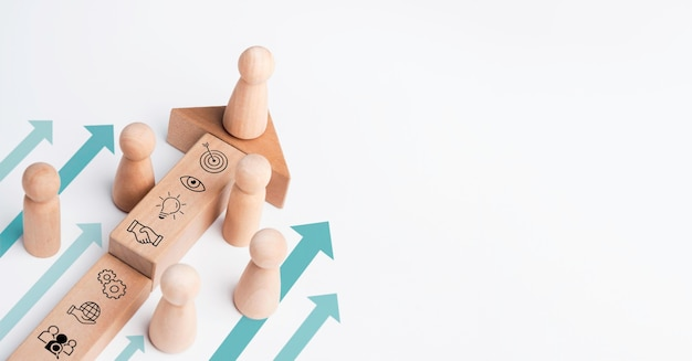 El líder, la figura de madera que lidera el equipo con el icono empresarial en un bloque de madera con flechas de dirección sobre fondo blanco con espacio de copia. estrategia empresarial con proceso de crecimiento exitoso, concepto de liderazgo.
