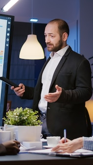 Líder de hombre enfocado explicando el proyecto de gestión usando el monitor trabajando en la sala de oficina de reuniones de la empresa ...