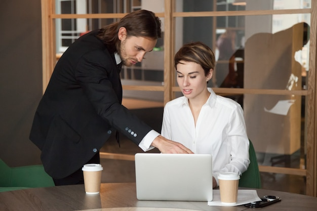 Líder masculino ayudando a un compañero ayudando con un inicio en línea