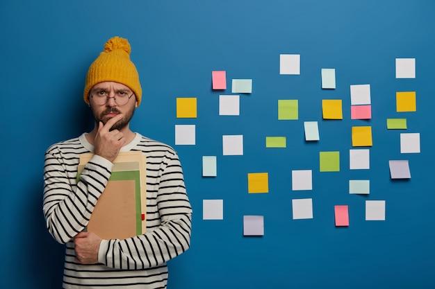 El líder mentor serio piensa en ideas creativas, sostiene la barbilla y mira directamente a la cámara, usa lentes redondos transparentes, se para con blocs de notas