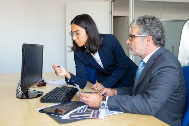 Líder de negocios masculino enfocado y asistente femenina mirando el informe estadístico en el monitor de la pc, sosteniendo gráficos comerciales de papel. vista lateral. concepto de expertos financieros