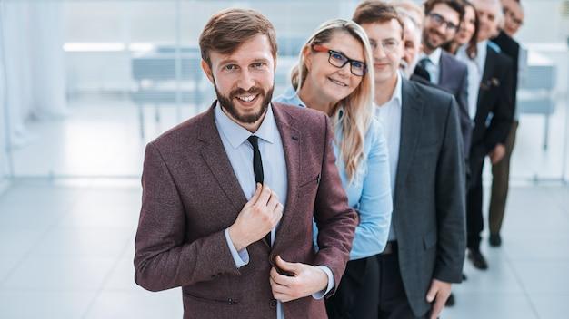 Líder seguro de pie frente al equipo empresarial. el concepto de trabajo en equipo