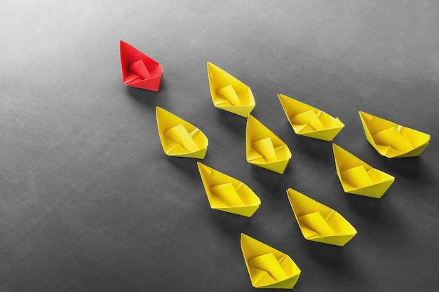 Liderazgo concepto rojo líder barco de papel que se destaca de la multitud de barcos amarillos
