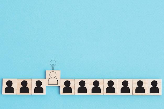 Liderazgo y pensar diferente concepto. personas en fila y un humano diferente con una lámpara de idea sobre su cabeza sobre fondo azul.
