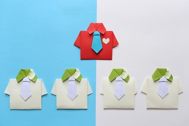 Liderazgo y trabajo en equipo, camisa roja de origami con corbata y líder entre una pequeña camisa amarilla en colores