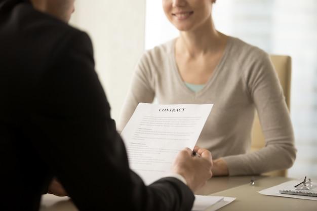 Líderes empresariales femeninos y masculinos estudian contrato