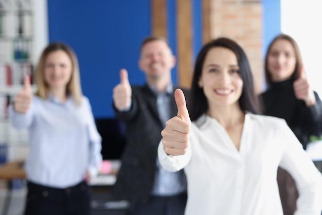 Líderes empresariales con grupo de empleados mostrando los pulgares para arriba