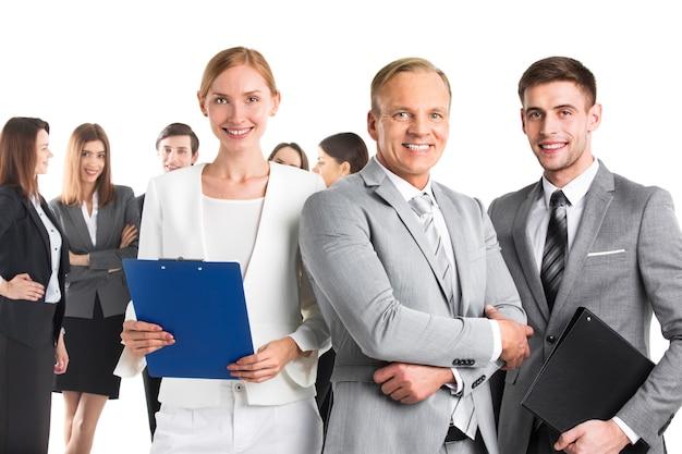 Líderes empresariales sonrientes y su equipo aislado en superficie blanca