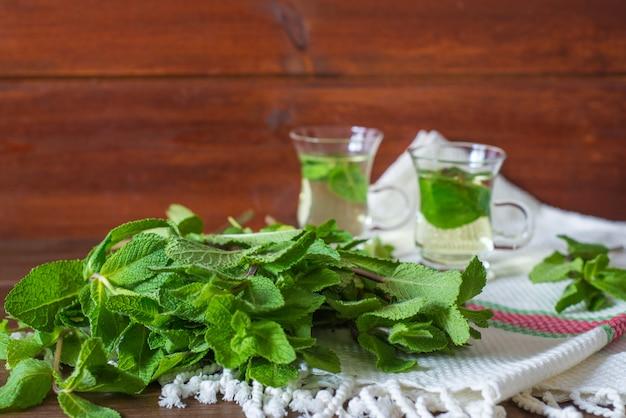 Liefs de menta con 2 tazas pequeñas de té de vidrio sobre fondo en mesa de madera