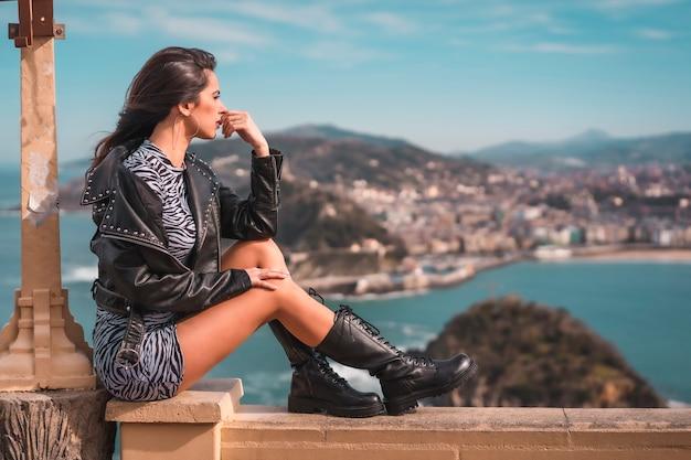 Lifestyle, una joven morena sentada en un vestido, botas y chaqueta con la ciudad al fondo