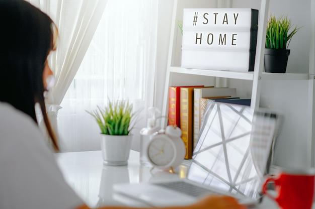Lightbox con el hashtag de texto #stayhome brillando en la luz y borrosa mujer que trabaja en casa. oficinista en cuarentena. inicio trabajando para evitar la enfermedad viral. concepto de trabajador independiente o remoto.