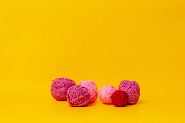 Lila, bolas de lana rosa se encuentran sobre un fondo amarillo