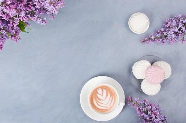 Lila, café con café con leche y malvavisco en la mesa de madera gris. mañana romántica lay flat