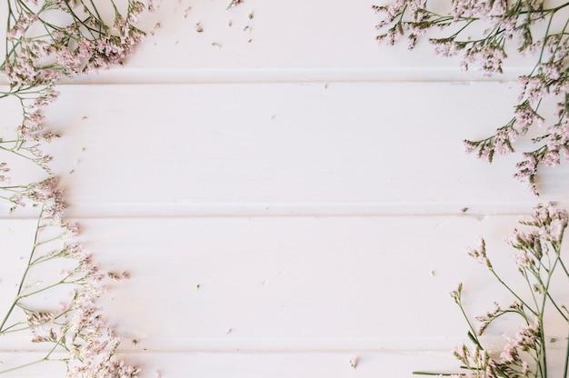 Lila pequeñas flores sobre una mesa de madera con espacio en el medio