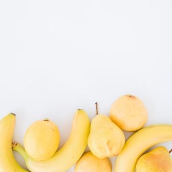 Lima amarilla; peras y plátanos aislados sobre fondo blanco