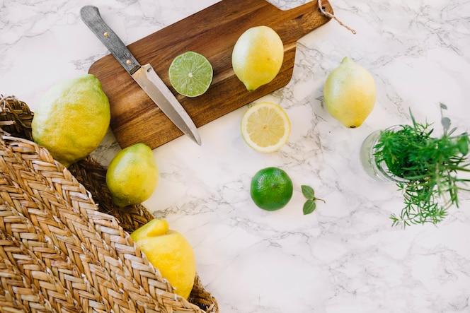 Lima en rodajas; limón y cuchillo en la tabla de cortar de madera
