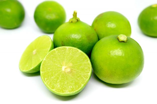Lima fresca en secciones transversales con frutas enteras dispersas
