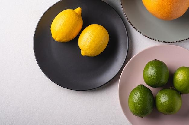 Lima, limón, pomelo en coloridos platos en blanco