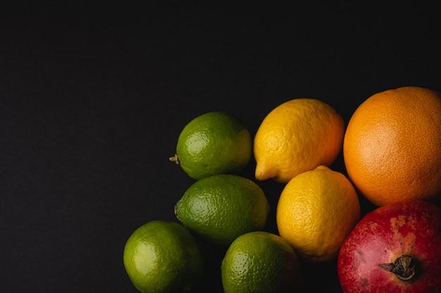 Lima, limón, pomelo y granada sobre negro oscuro cambiante