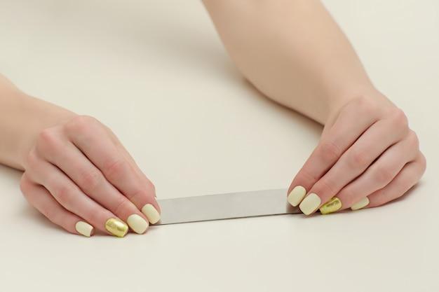 Lima de uñas en manos femeninas, lugar para el texto. fondo blanco