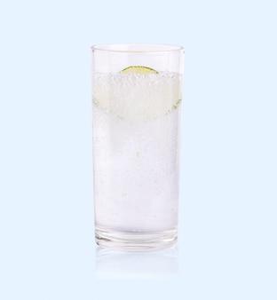 Lima verde en rodajas cayendo en el agua de soda de vidrio en el azul suave