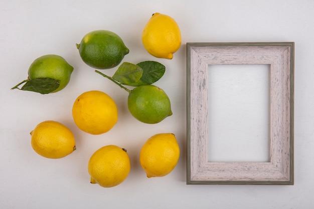 Limas de espacio de copia de vista superior con limones y marco gris sobre fondo blanco