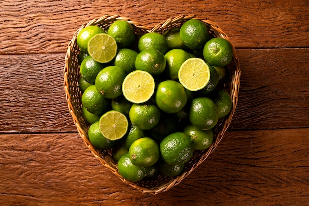 Limas frescas en un tazón de corazón sobre fondo de mesa de madera. vista superior.
