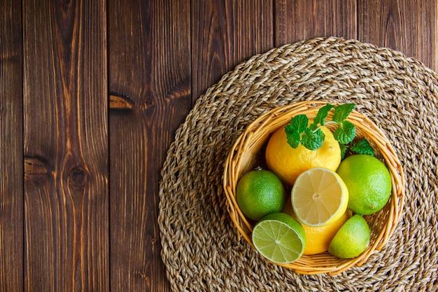 Limas con limones, hierbas en una cesta de mimbre sobre mesa de madera