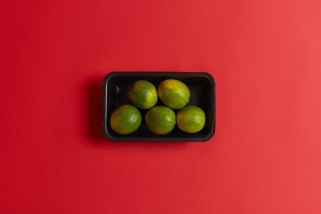 Limas verdes frescas listas para la venta en supermercados o mercados, empaquetadas en prueba negra, aisladas sobre fondo rojo. frutas maduras para preparar compota, limonada, cóctel, bebida ácida de verano. luz natural