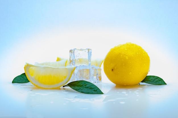 Un limón amarillo entero fresco, rodajas de limón, hojas verdes, cubos de hielo frío y sobre un fondo azul. aislado.