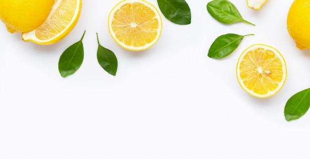 Limón fresco y rodajas con hojas aisladas en blanco.