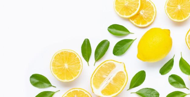Limón fresco y rodajas con hojas aisladas en blanco