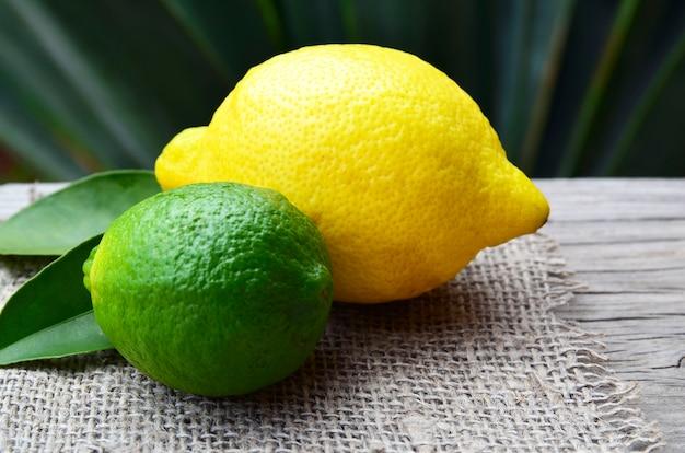Limón y limón frutas orgánicas maduras frescas sobre fondo de madera vieja. concepto de aromaterapia o alimentación saludable.