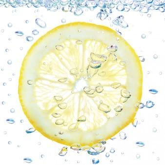 Limón en un líquido con burbujas. en una pared blanca