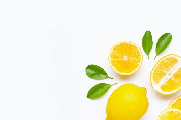Limón y rodajas con hojas aisladas en blanco.